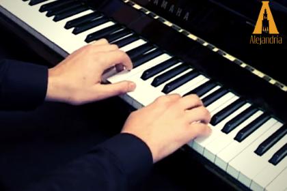 Manos tocando un piano al componer una canción